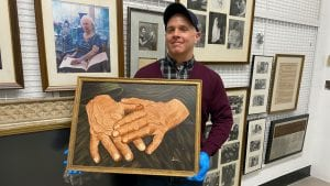 A man wearing a sweater and a baseball cap holds the same painting. He is wearing blue latex gloves to protect the painting from fingerprints. On the wall behind him hang various framed photos of Helen Keller.