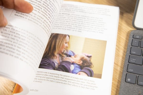 Babies with CVI book is held open to a page that includes an image of a woman and infant