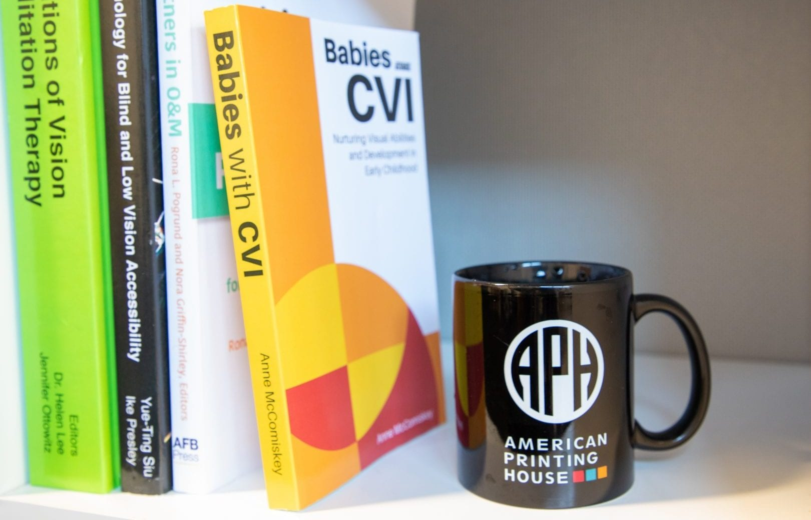 babies with CVI book sits on a bookshelf with other APH Press books. a black APH coffee up sits next to them.