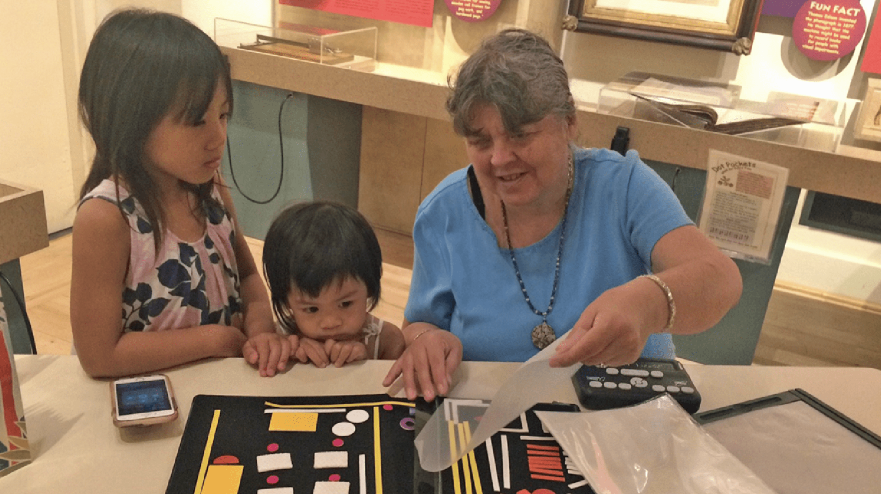 """Two children stand next to a woman who is showing them """"Picture-Maker,"""" or the Wheatley Tactile Diagramming Kit"""