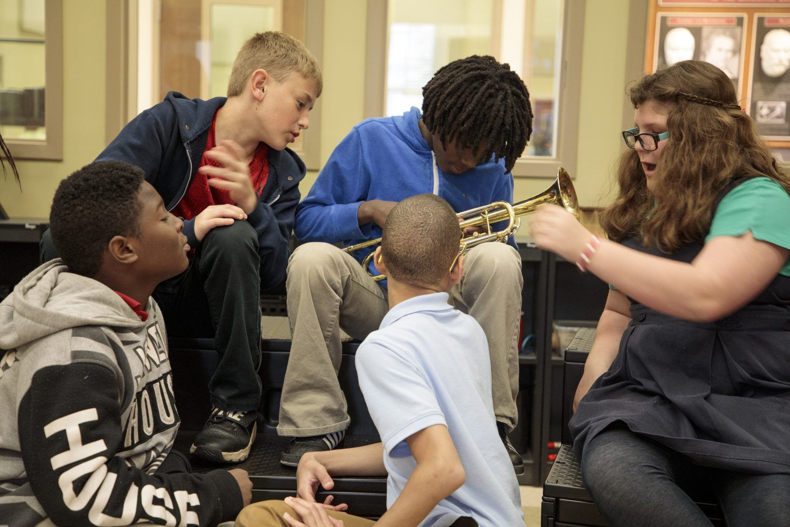 a group of students sitting together in a music classroom talking. one of them holds a trumpet.