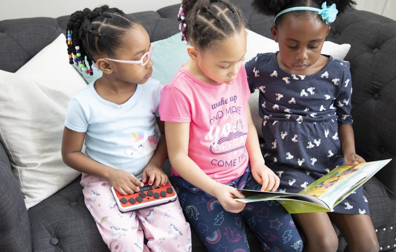 three girls reading on a couch. two are looking at a print book and one is using the braille trail reader
