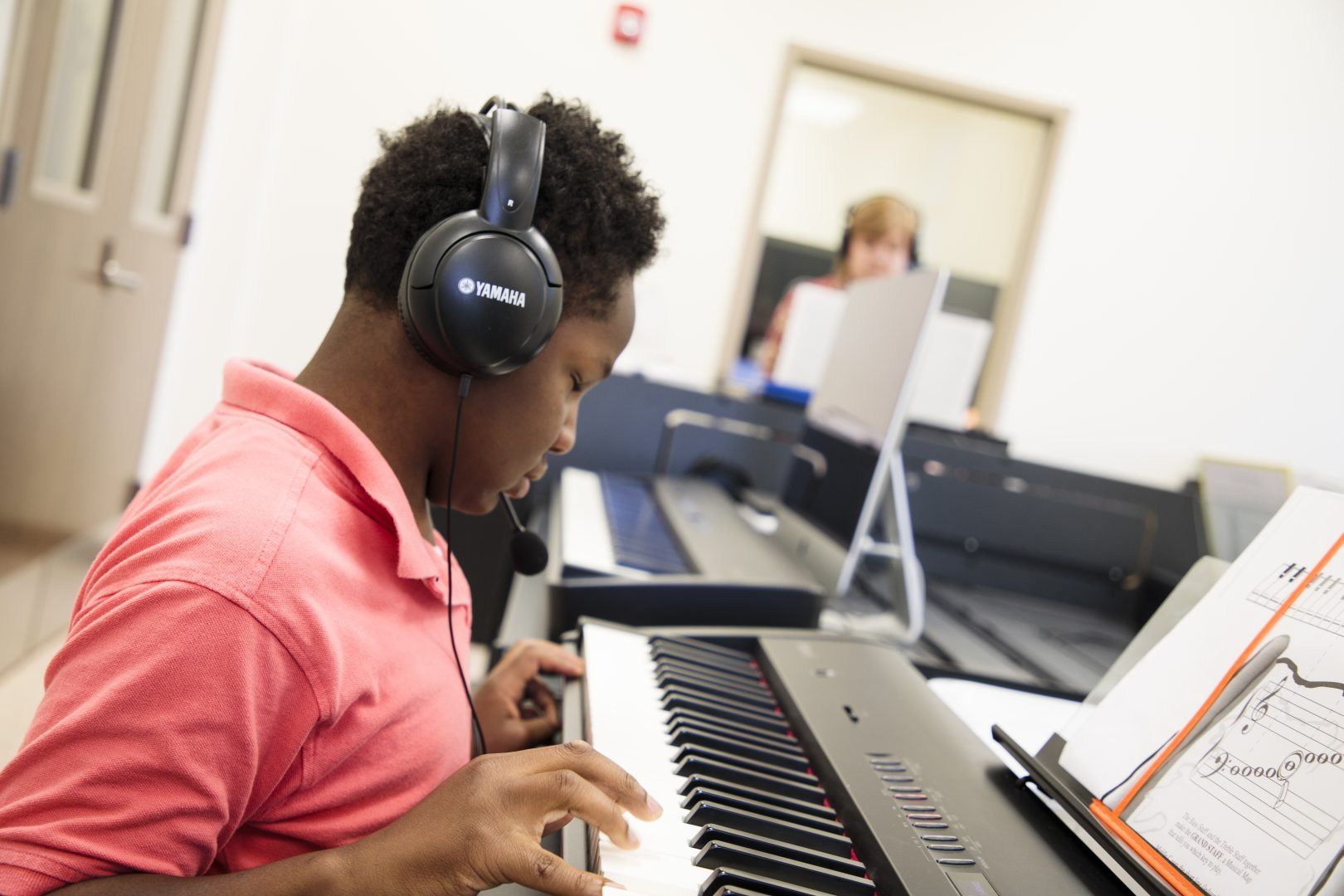 an elementary aged student playing and keyboard and wearing headphones. A teacher can be seen in the background.