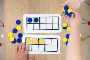 a student uses ten frames and blue and yellow textured discs to do math equations within the plastic frames
