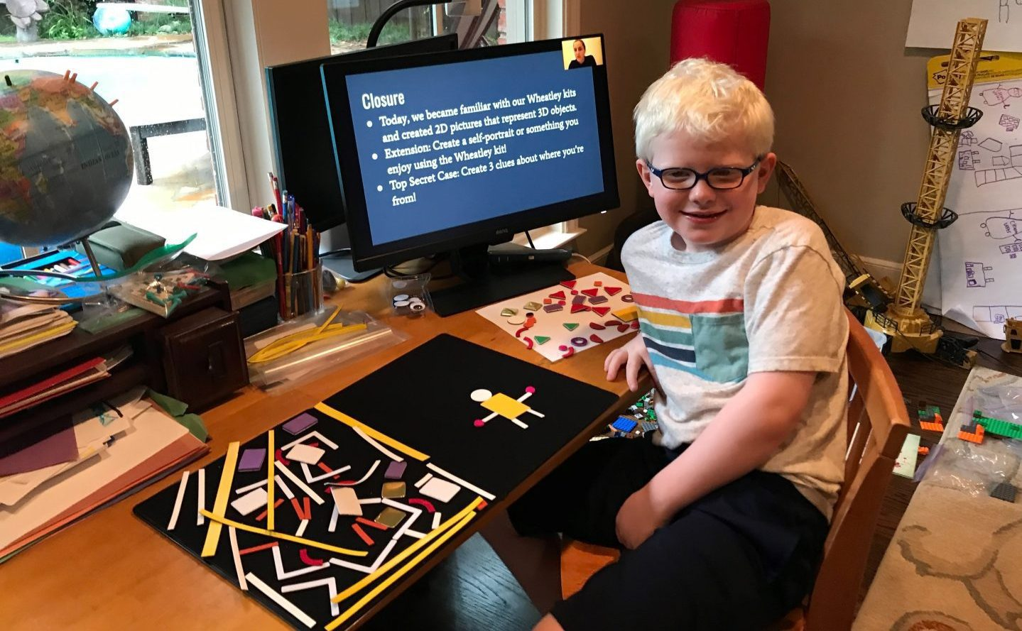 a student smiling in front of a computer with a presentation on the screen. the Picture Maker Wheatley Tactile Diagramming Kit sits on the table next to them showing extra pieces to the left and the figure of a person on the right.