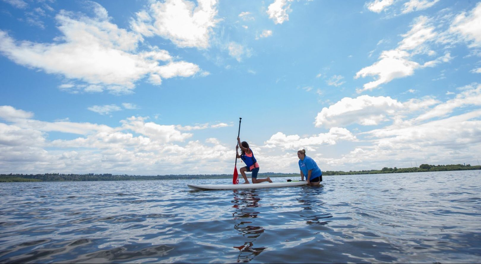 stacey standing in a body of water helping a student on a paddle board