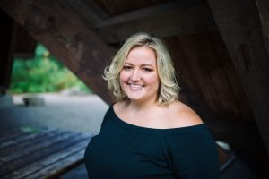 a portrait style photo of Stacey smiling in a black blouse in front of an old wooden structure