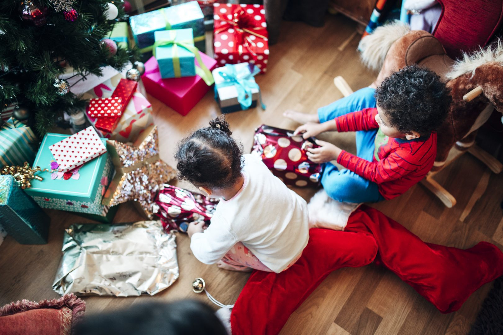 birds eye view of two children sitting on the floor opening colorful presents in front of a christmas tree