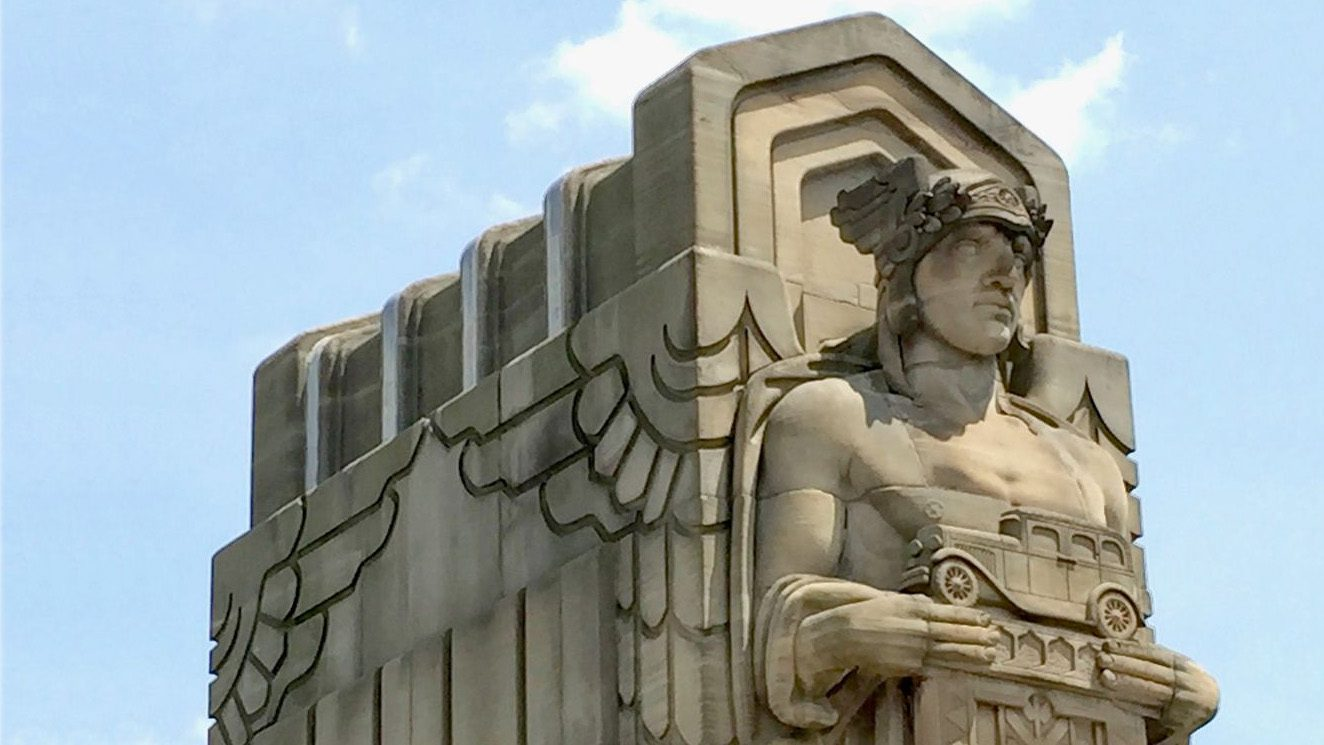 Statue of a man in front of a wall. He is wearing a crown of leaves, with wings at either side, and holding a model of a 1930s automobile.