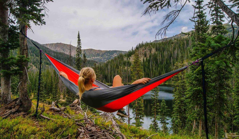 A young woman hammock camping