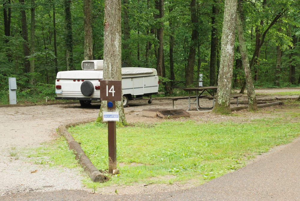a pop up camper parked in a campsite