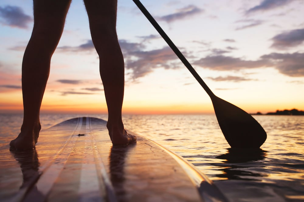A person stand up paddle boarding at sunset