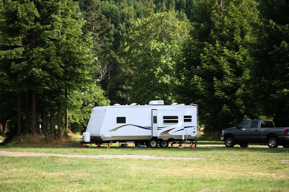 A travel trailer RV with expandable sides parked