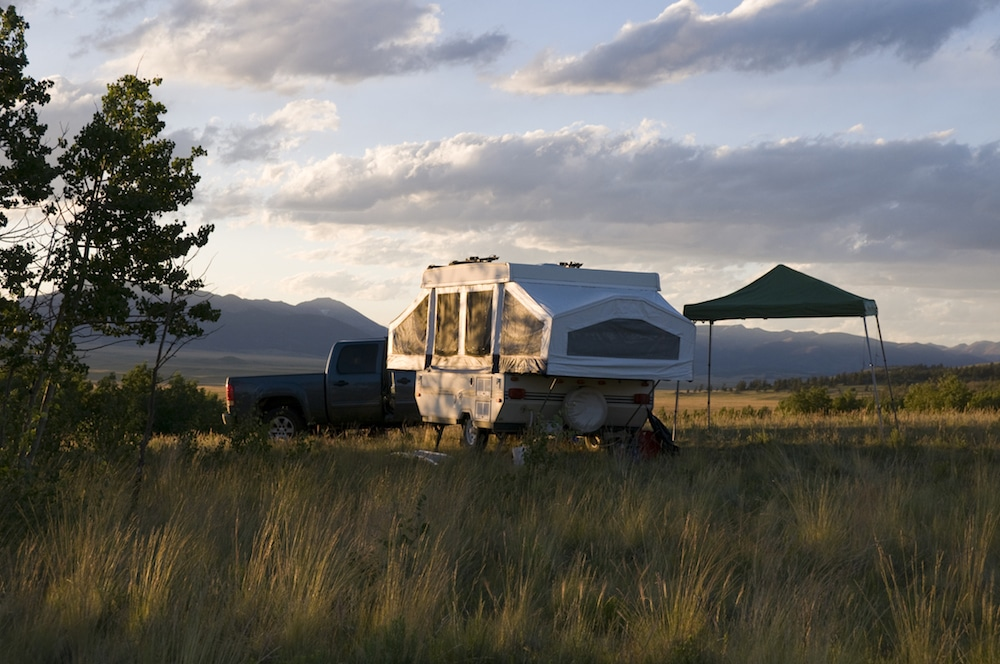 A pop-up camper set up next to a truck and an awning