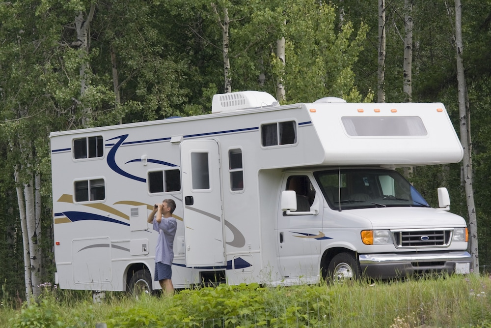A man standing outside his Class C RV