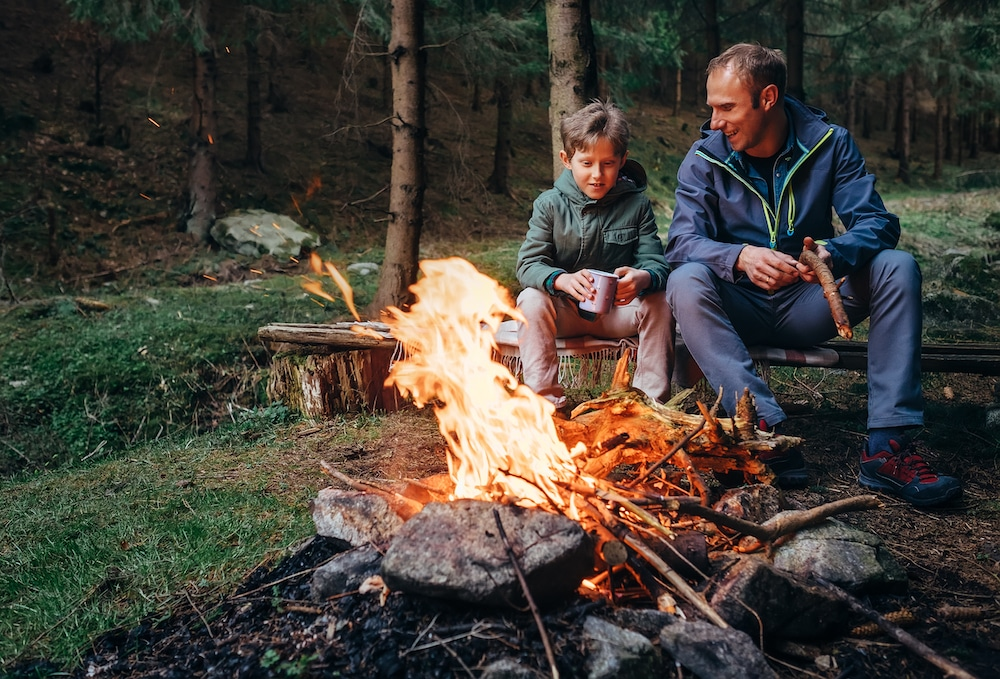 A father and son sitting around a camp fire.