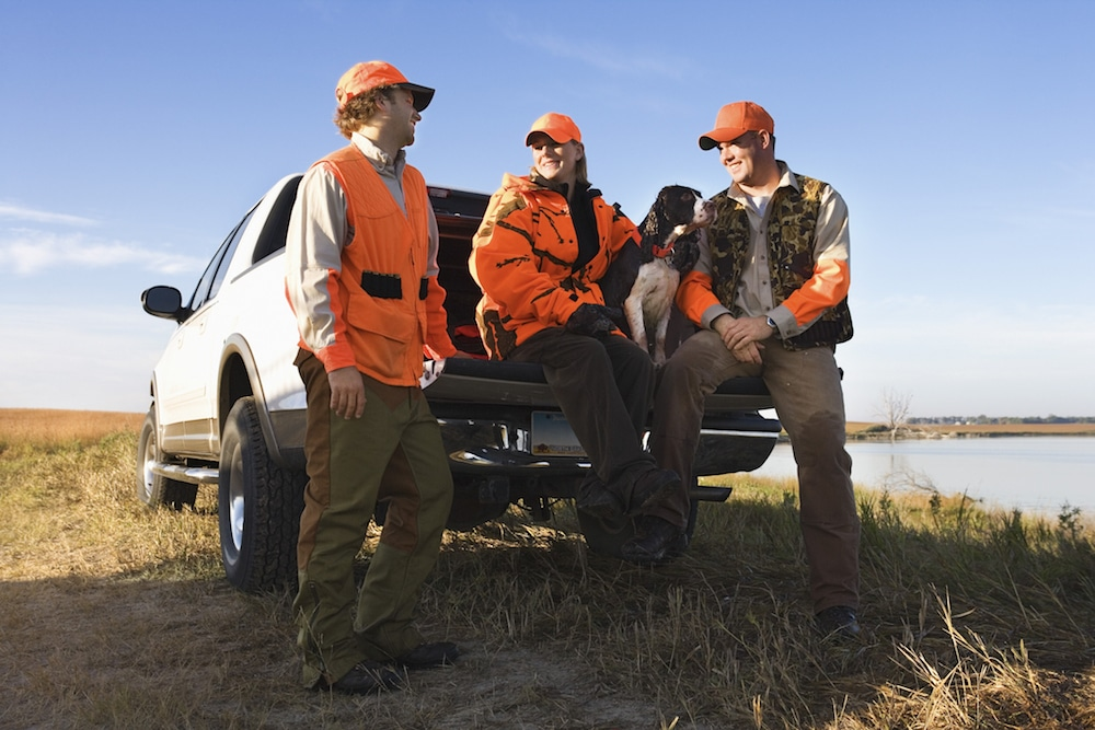 Three people wearing blaze orange sitting on a pickup truck tailgate