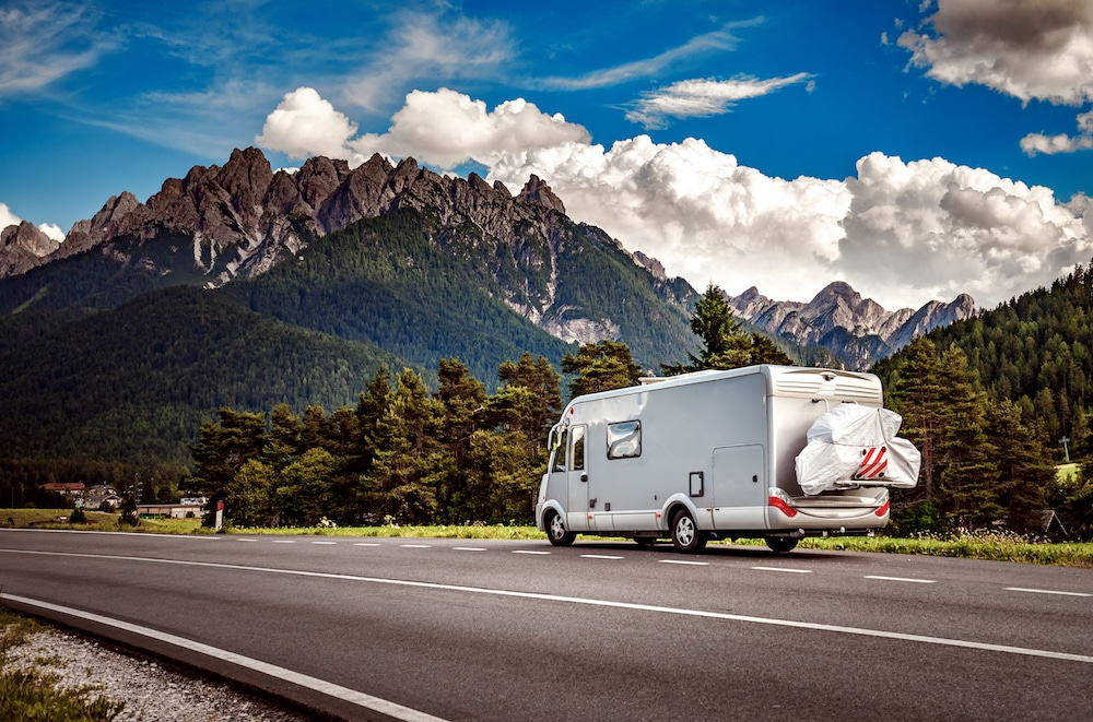 Class A RV driving on a road with mountains in the background