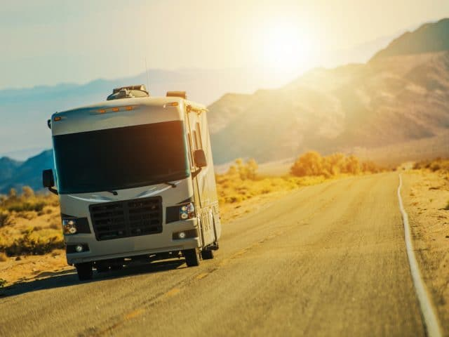 A Class A RV driving on the open road.