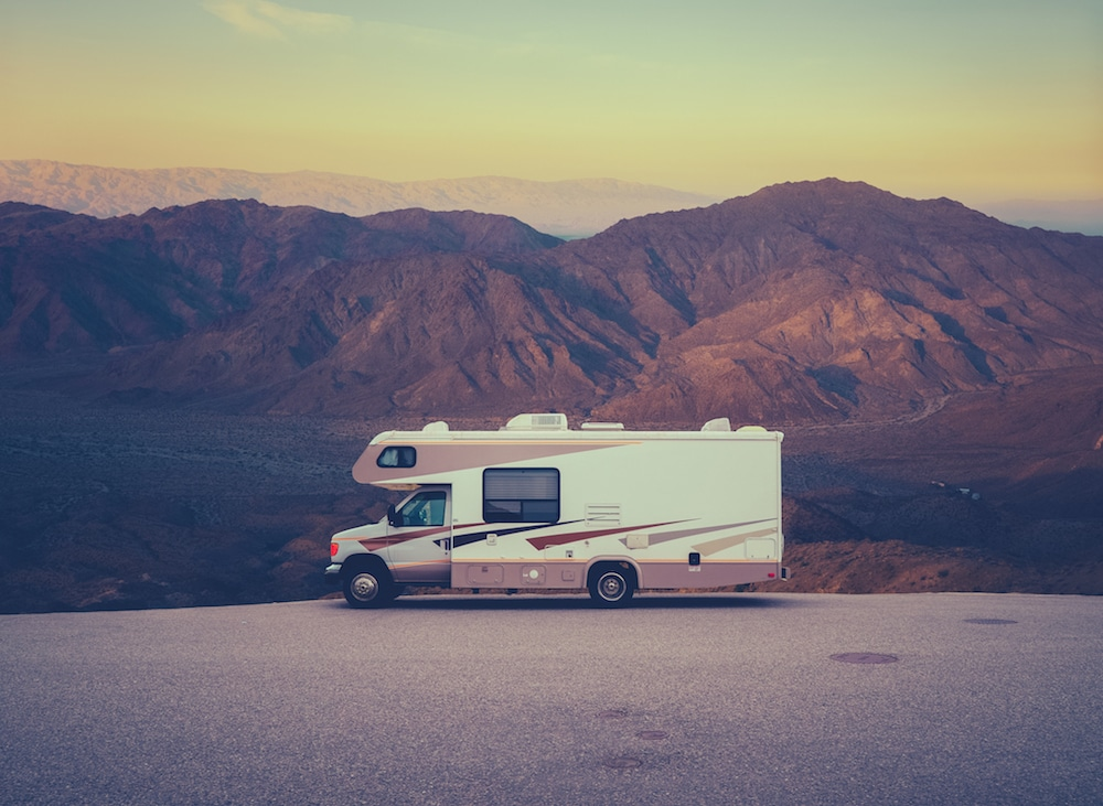 Class C RV parked near the mountains