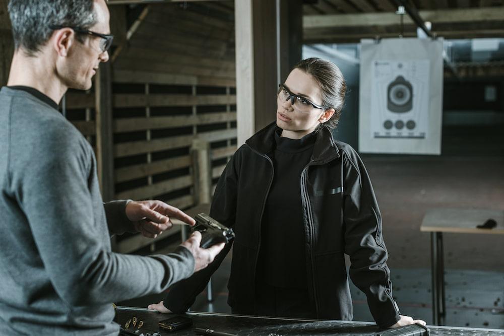 a man at a gun range instructing a woman