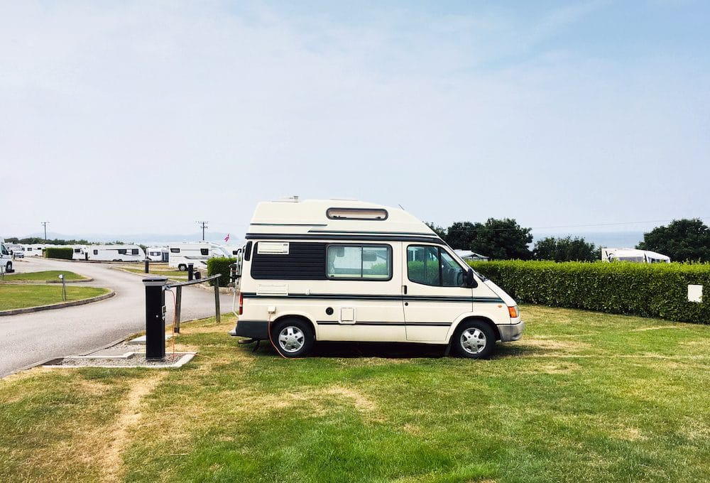 Camper van on campsite connected to electric hook up in NorthWales United Kingdom