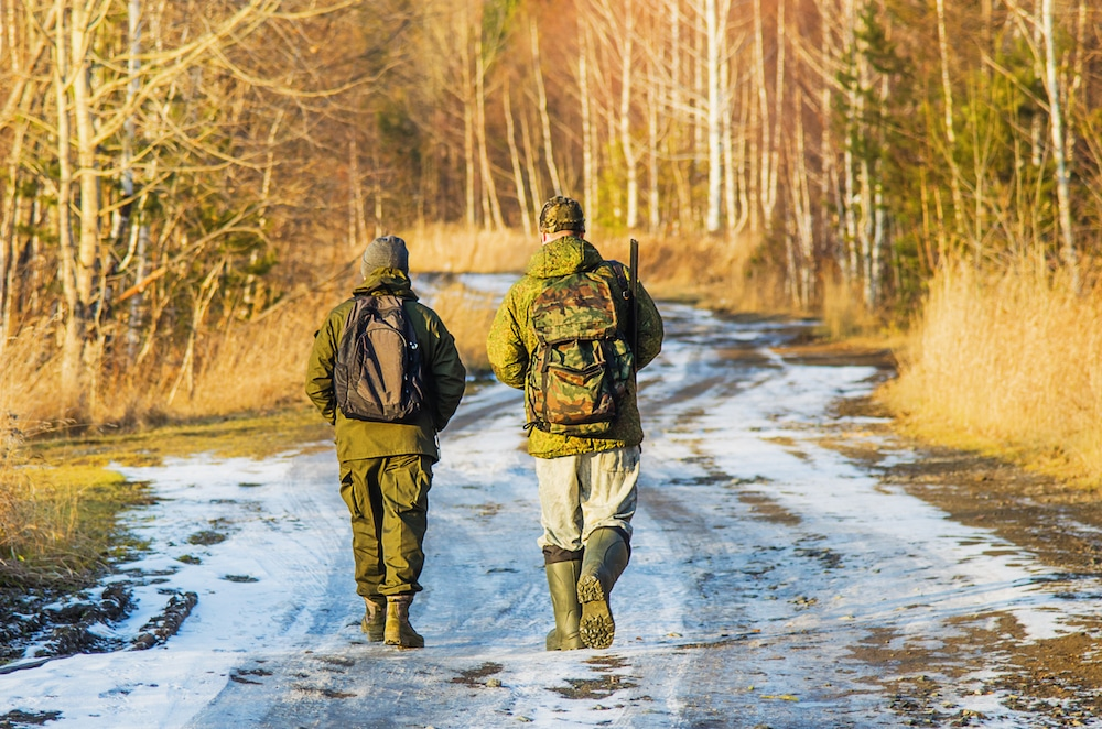 Two hunters walk along the forest road on a Sunny evening in late autumn