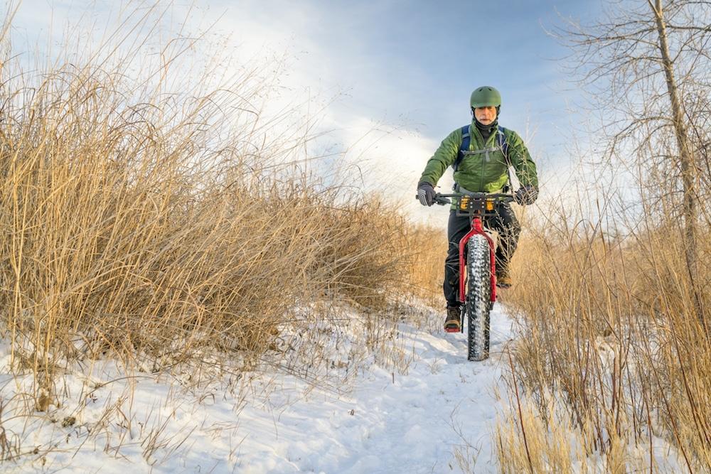 A man riding his fat bike on a snowy path