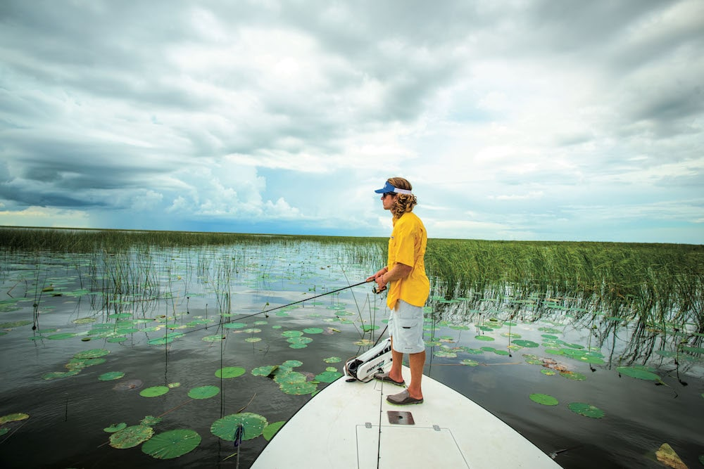 A man standing on a boat bass fishing