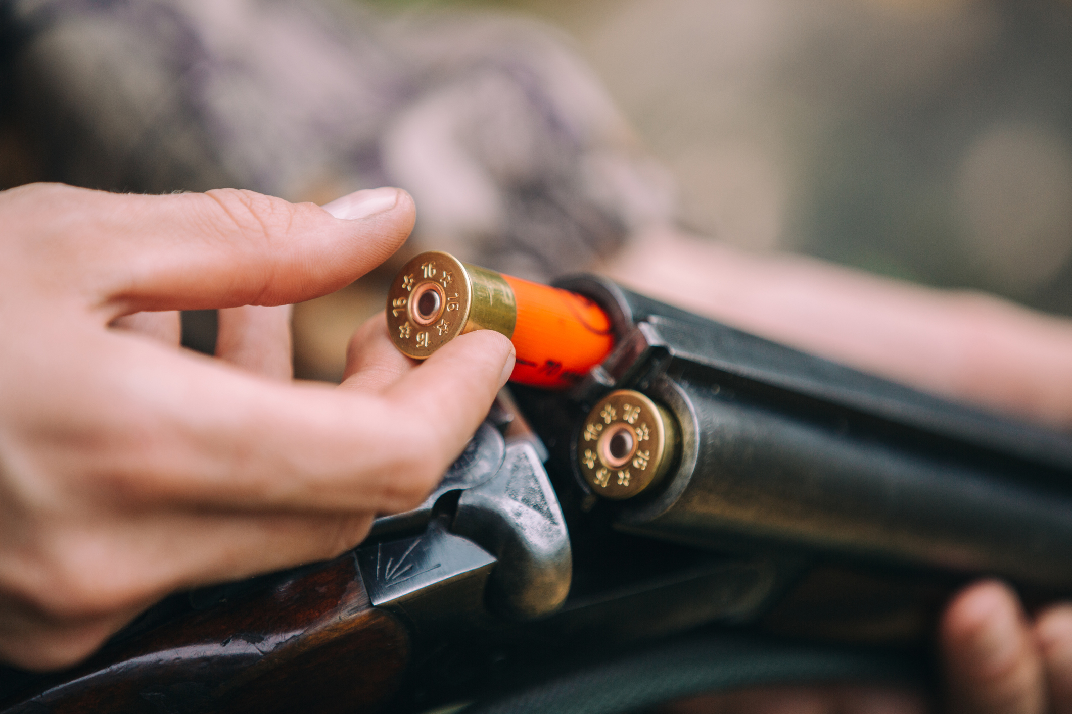 A man loading shotgun shells into a double barrel shotgun