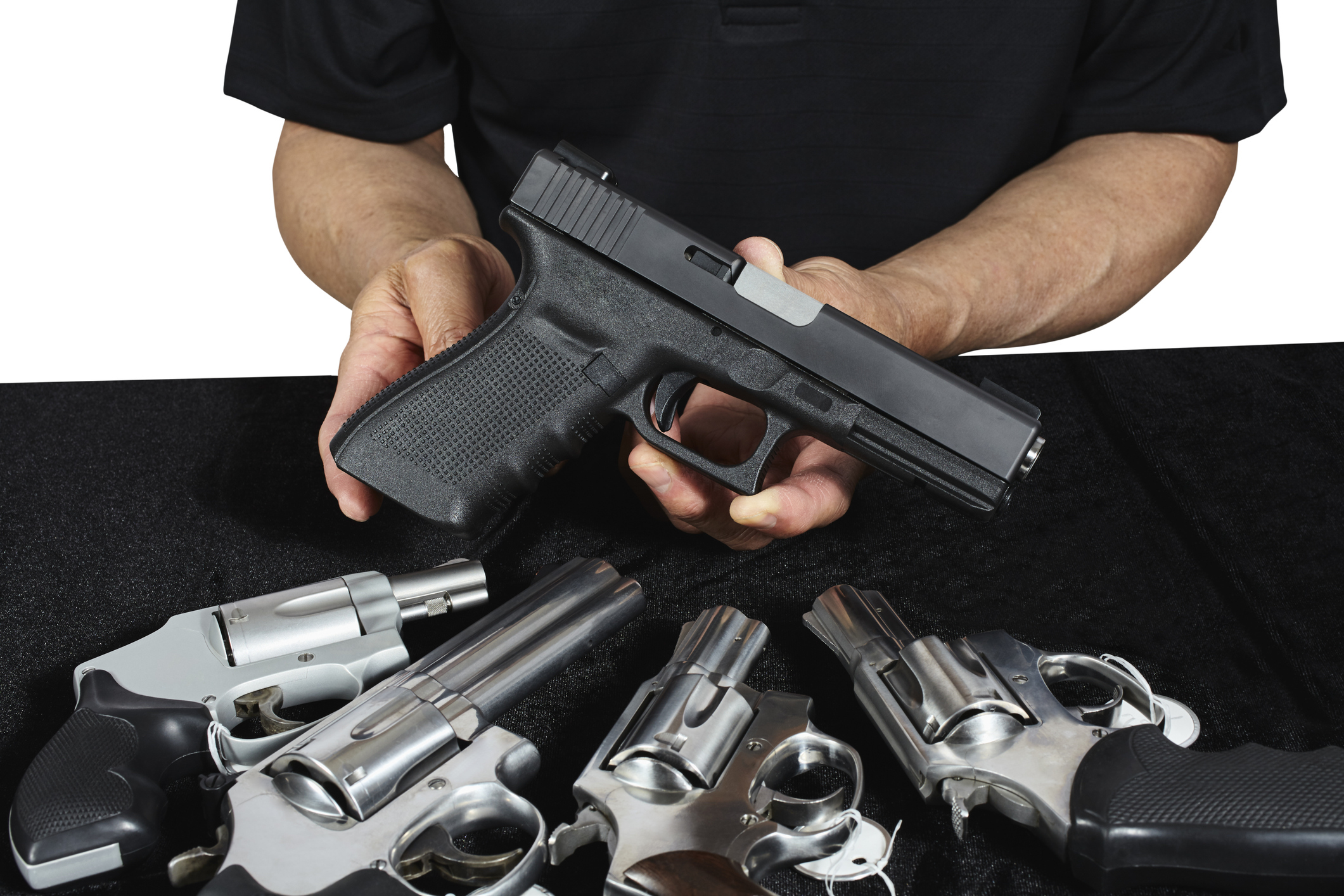 A man holding a semi-automatic handgun next to revolvers