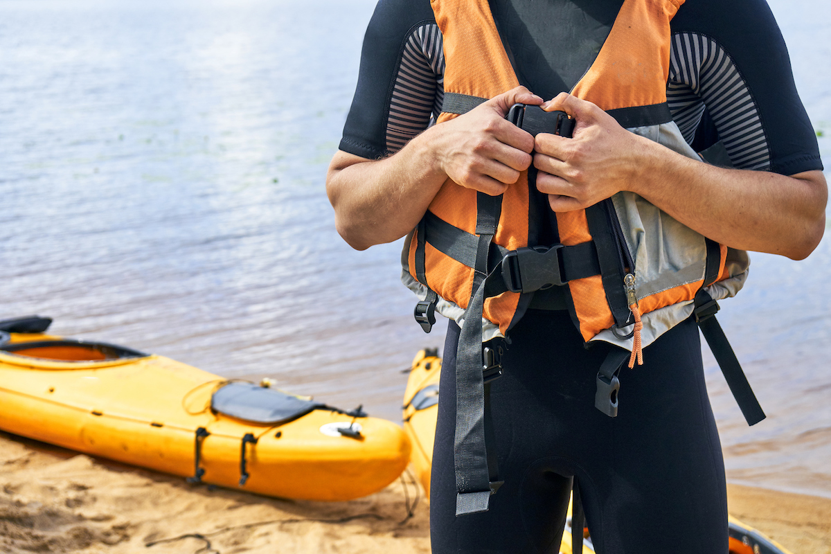 Male hiker wearing wetsuit putting on a life vest
