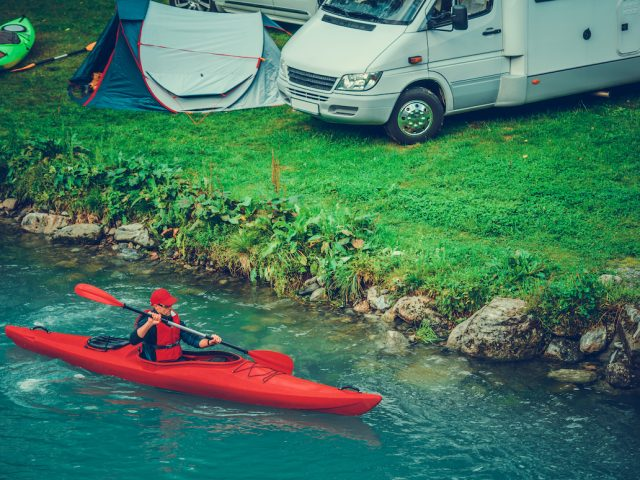 Waterfront RV Camping with Kayaking. Caucasian Sportsman in the Kayak on Glacial Lake.