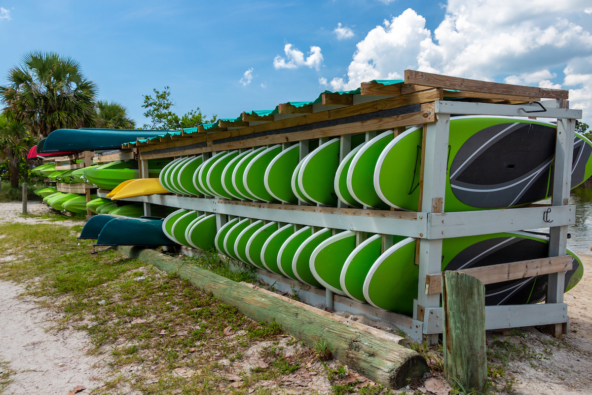 Rows of paddleboards, kayaks and canoes for rent