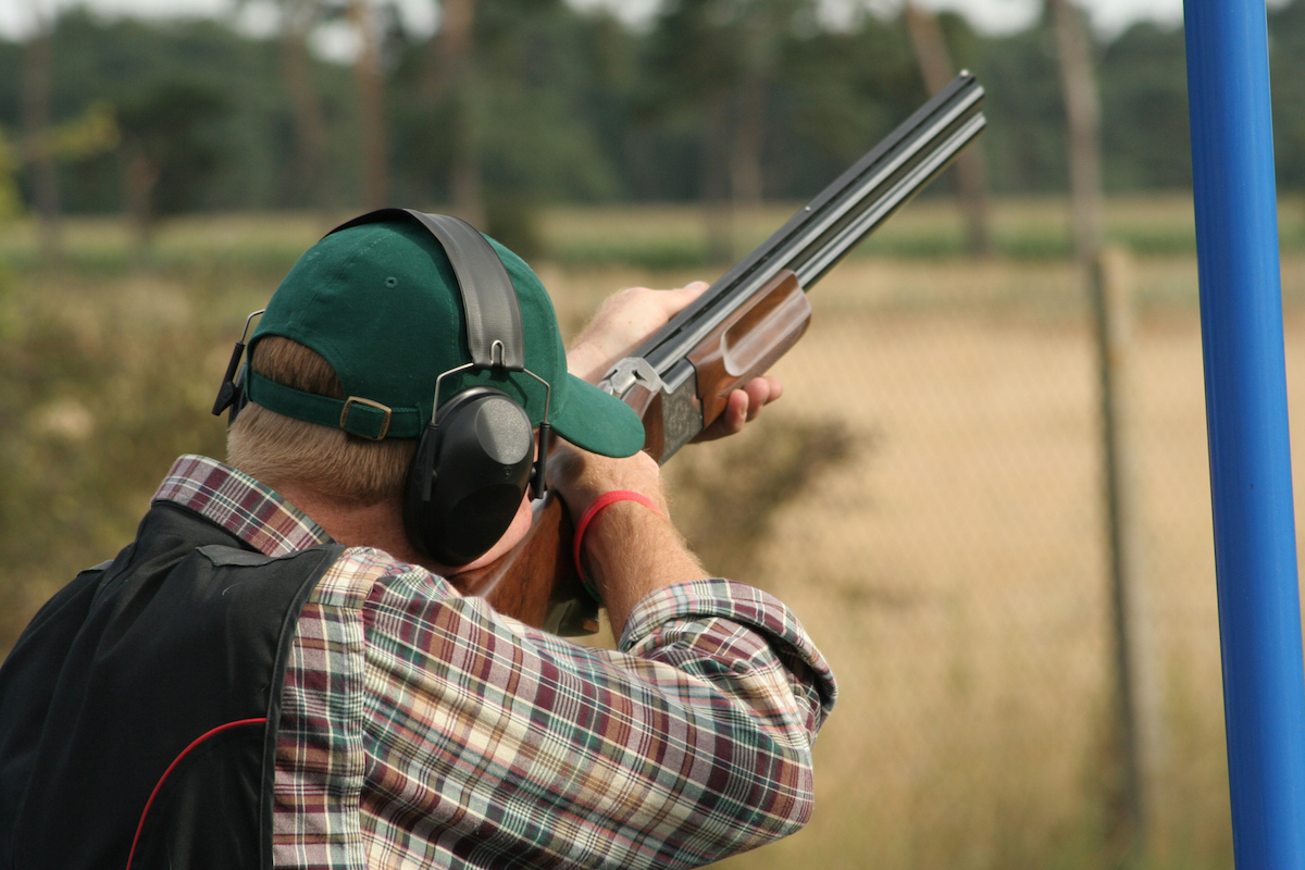 A male clay shooter holding a gun at his shoulder