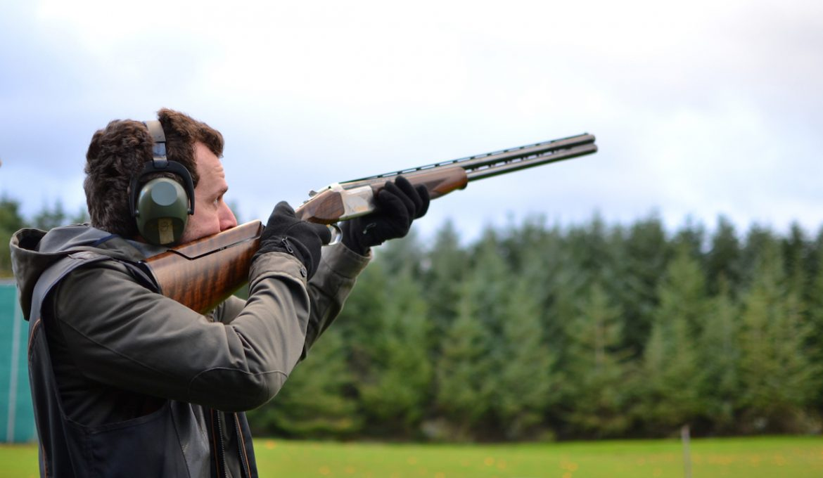 A man shooting a shotgun at clay pigeons