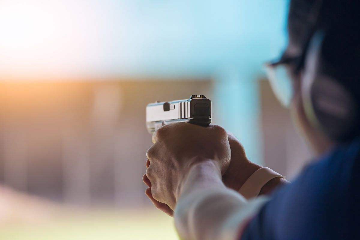 a man shooting a pistol at a shooting range