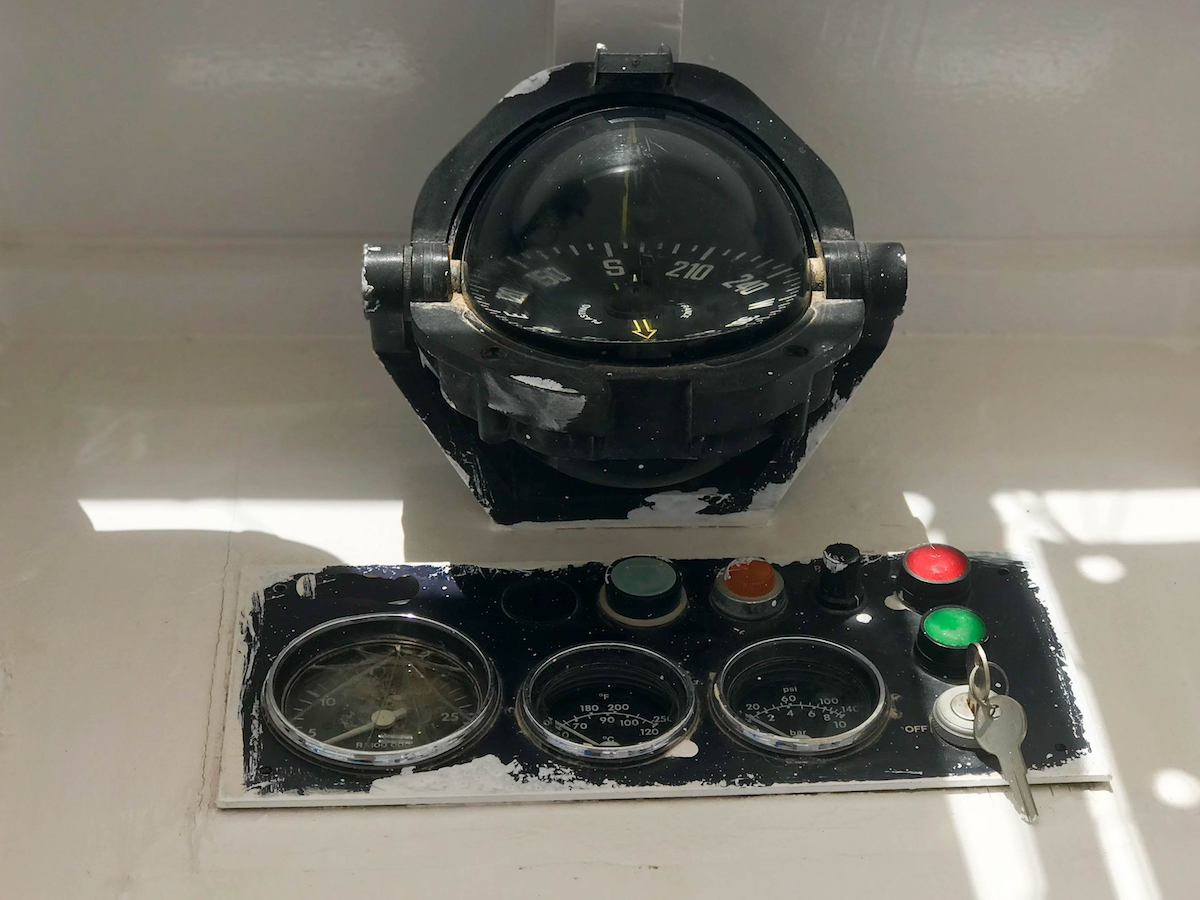 Instrument panel on a boat, ship, maritime transport with a compass, a tachometer, a speedometer, an ignition key and buttons