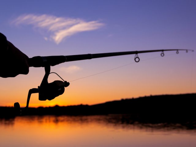 A rod and reel at sunset
