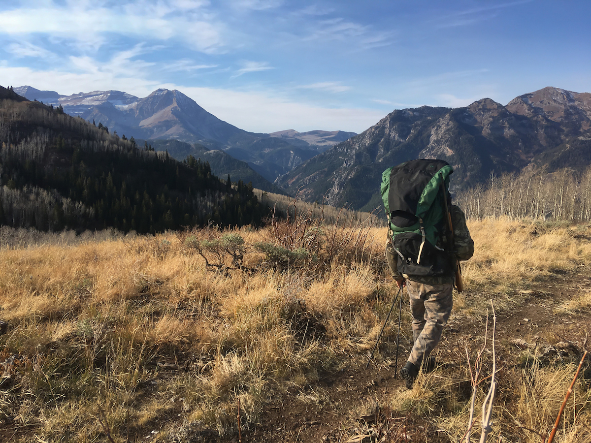 A hunter carries a large backpack as he hikes along a mountain ridge.