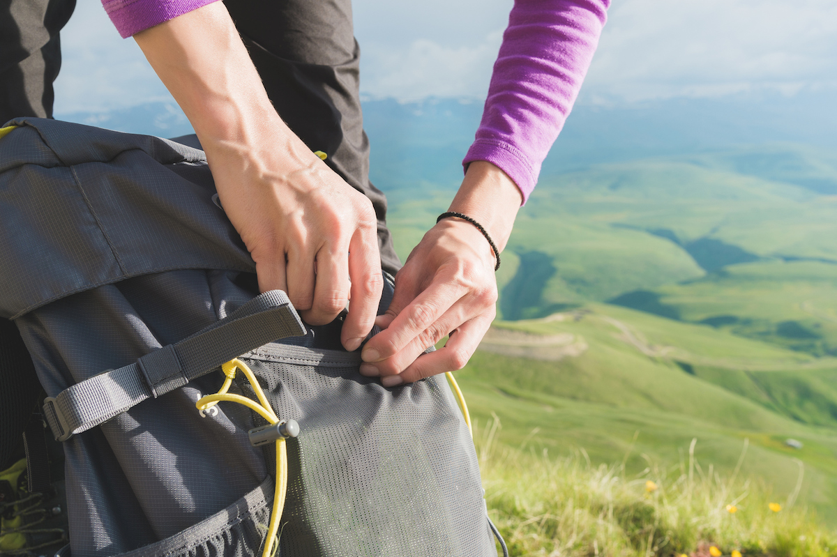 Close-up of women's hands unfasten the buckle on the camp backpack against the background of the valley in the setting sun. Tourism. Tracking