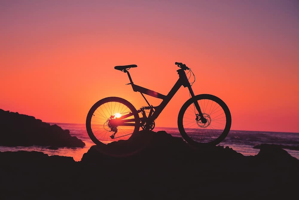 A mountain bike on top of a hill at sunset