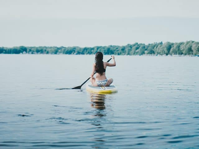 Woman sitting on paddleboard on a lake