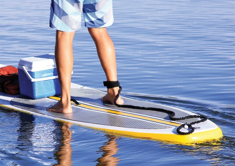 Man using paddle board leash