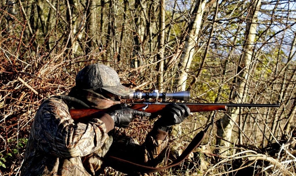 Man shooting a rifle while hunting