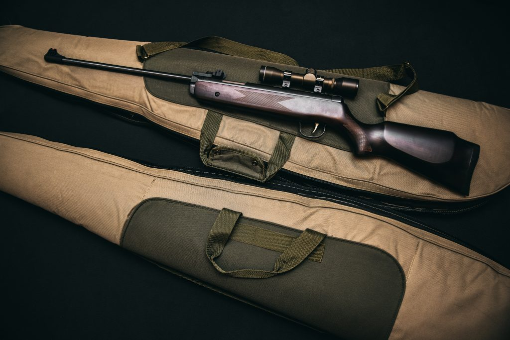 Rifle with walnut stock resting on rifle bag