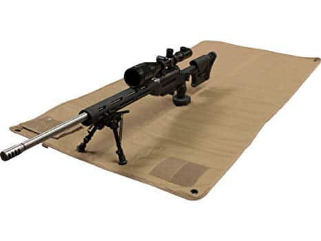 sniper rifle sitting on shooting mat.