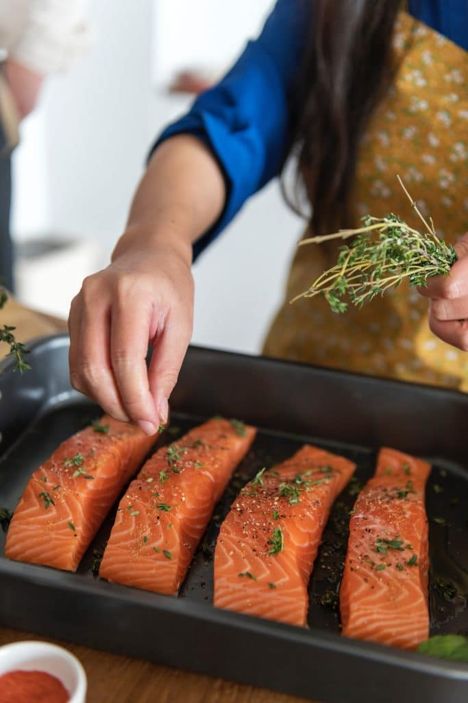 person seasoning salmon in a non-stick tray before cooking