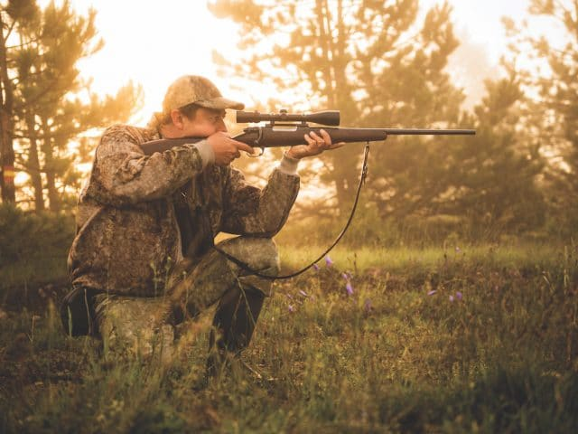 Portrait of a hunter while crouching and aiming with rifle at his prey.