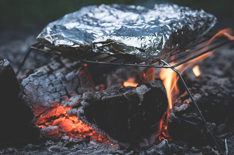 Foil packets over a campfire